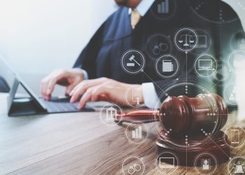 justice and law concept.Male judge in a courtroom with the gavel,working with digital tablet computer docking keyboard on wood table,virtual interface graphic icons diagram